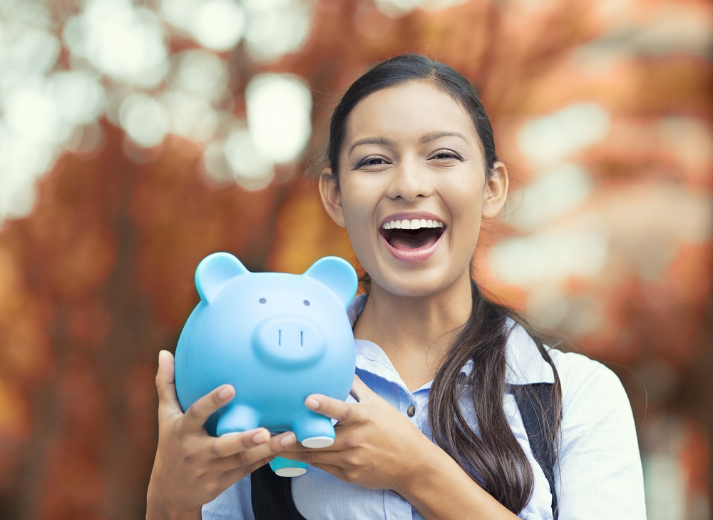 Closeup portrait happy, smiling business woman, bank employee holding piggy bank, isolated outdoors indian autumn background. Financial savings, banking concept. Positive emotions, face expressions-1