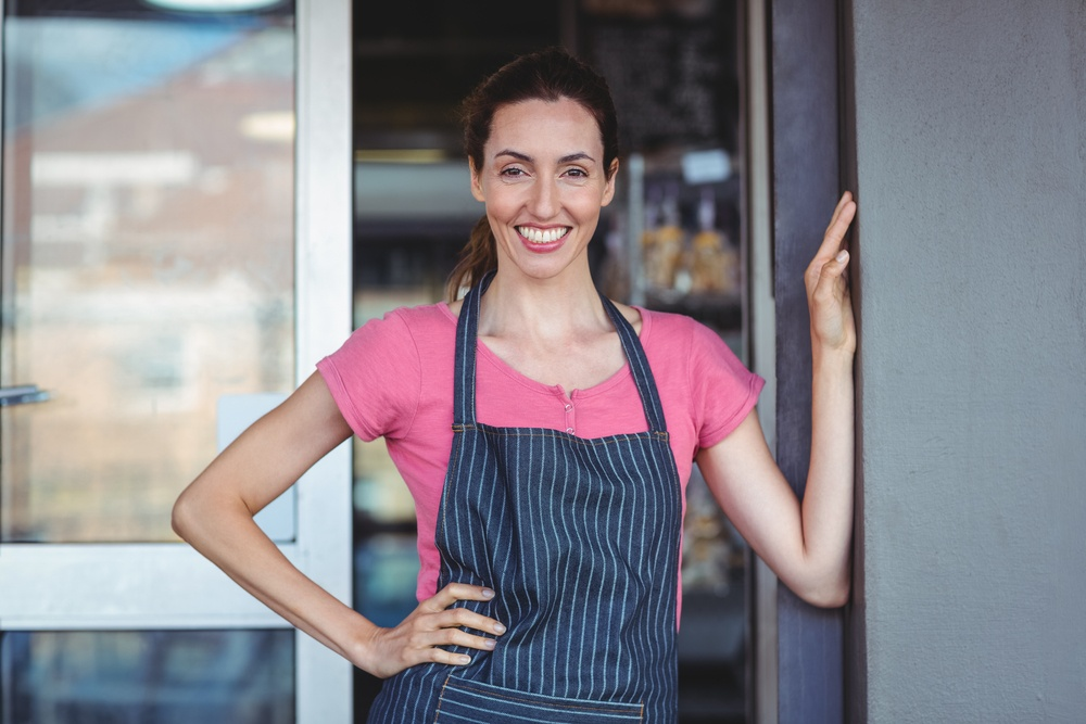Pretty waitress leaning on the wall at the bakery